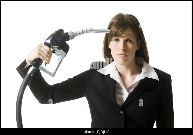 woman holding a gas pump to her head - Stock Image