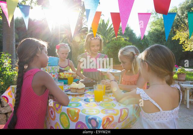 Girl serving friends birthday cake - Stock Image