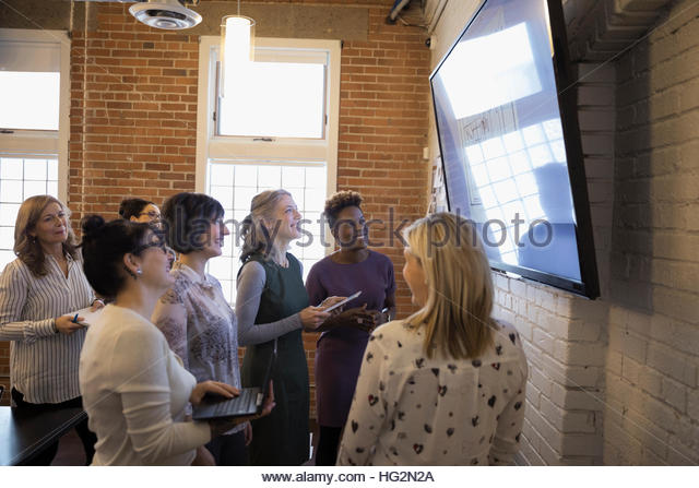 Businesswomen meeting at television monitor in conference room - Stock Image