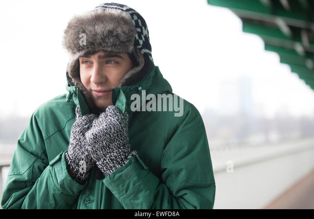 Man in warm clothing shivering outdoors - Stock Image