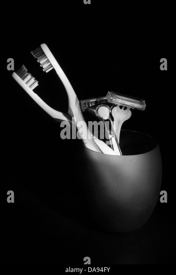 A pair of toothbrushes and razors. - Stock Image