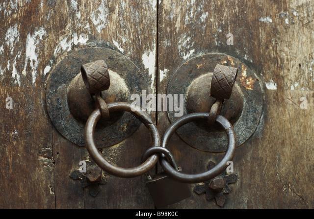 Old wooden doors, close-up of iron door handles linked by padlock - Stock Image