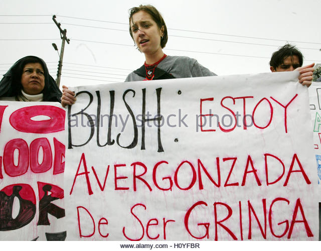 A U.S. citizen holds up a protest banner that reads: 'Bush, I'm  embarassed to be a 'gringa'' - Stock Image