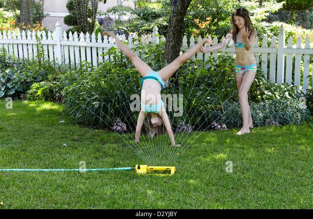 Sisters playing in water from sprinkler - Stock-Bilder