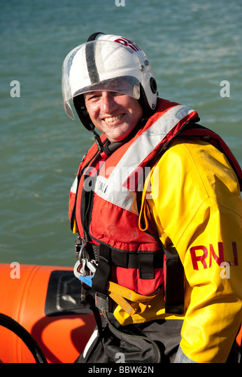 Male RNLI inshore rescue lifeboat crew member wearing full safety jacket buoyancy jacket and helmet - Stock Image