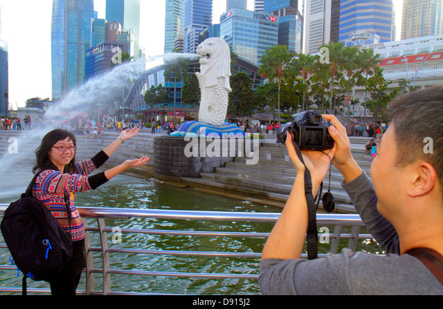 Singapore Singapore River Marina Bay Merlion Park Asian man woman posing taking picture camera - Stock Image