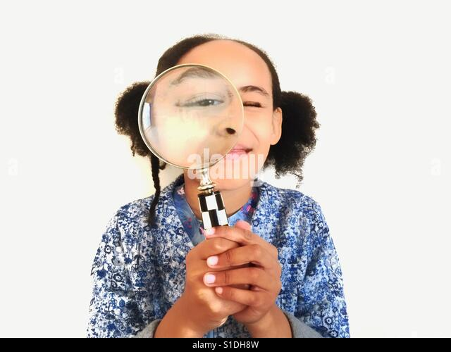 A young girl looks through a magnifying glass. - Stock-Bilder
