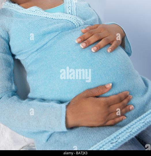 Pregnant woman holding her swollen abdomen. - Stock Image