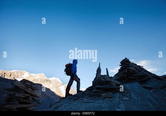 silhouette of hiker climbing mountain peak at sunrise - Stock Image
