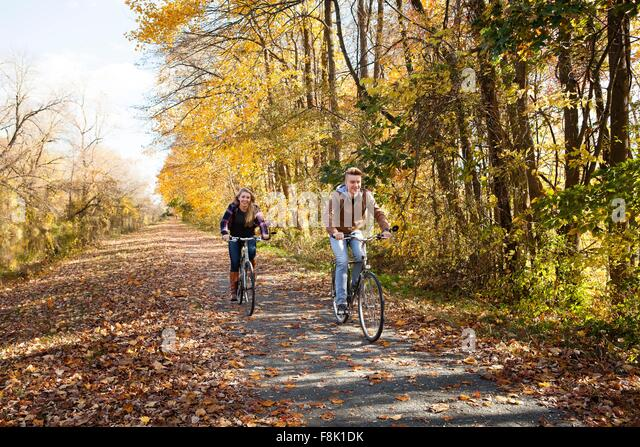 Teenage boy and adult sister cycling along autumn forest road - Stock Image