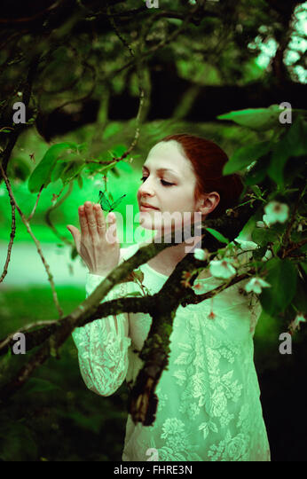 young woman in the forest holding a butterfly - Stock Image