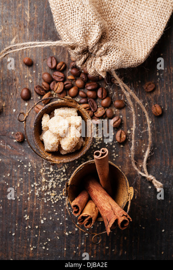 Cinnamon sticks, cane sugar and coffee beans on wooden background - Stock Image