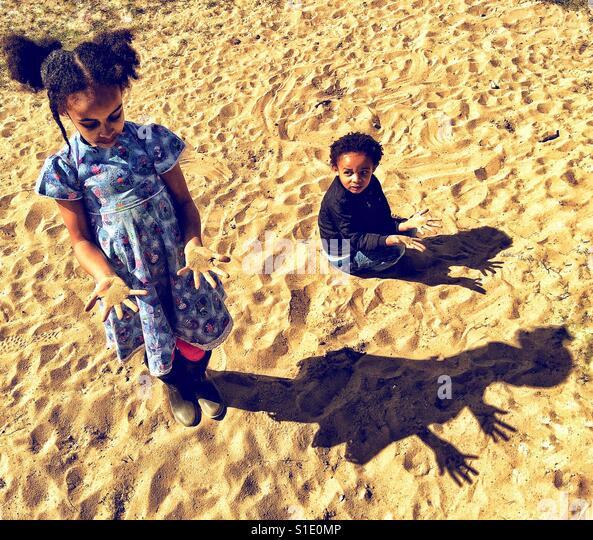 Children making shadows on the sand. - Stock-Bilder