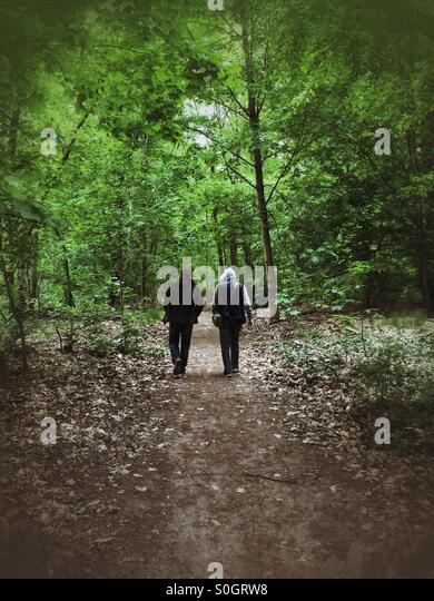 Two men walking in the woods - Stock Image