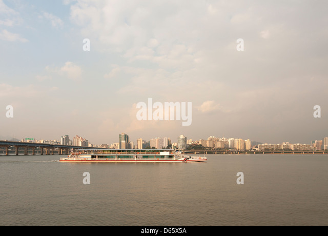 A river boat on Han river in Seoul, South Korea, during the golden hour. Seen from the Yeouido island. - Stock Image