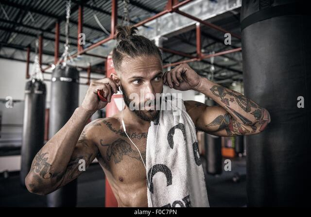 Male boxer putting in earphones at gym - Stock-Bilder