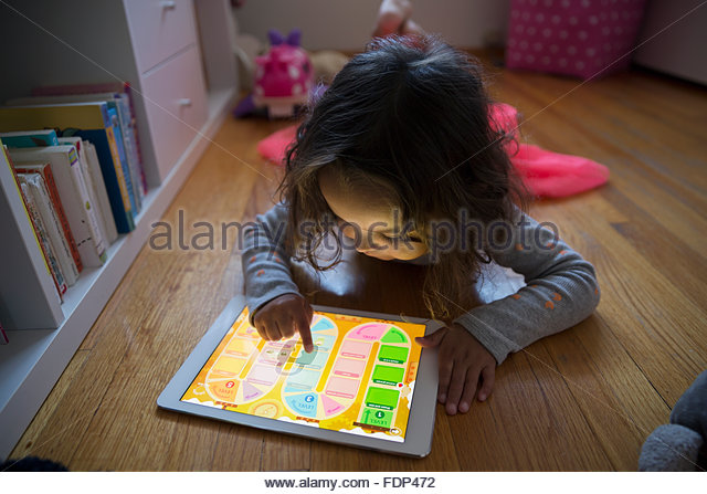 Girl playing game on digital tablet on floor - Stock Image