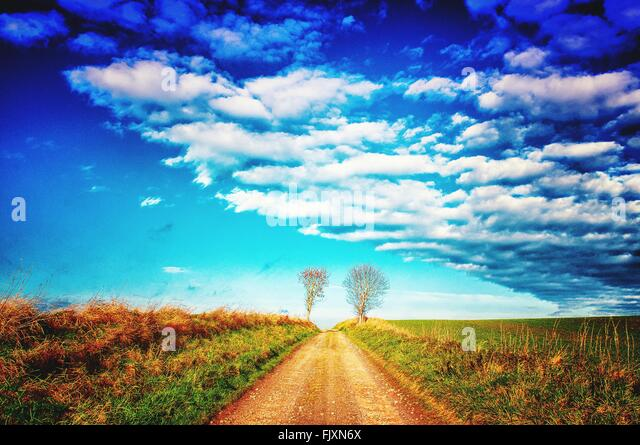 Empty Road Amidst Grassy Landscape Against Cloudy Sky - Stock Image