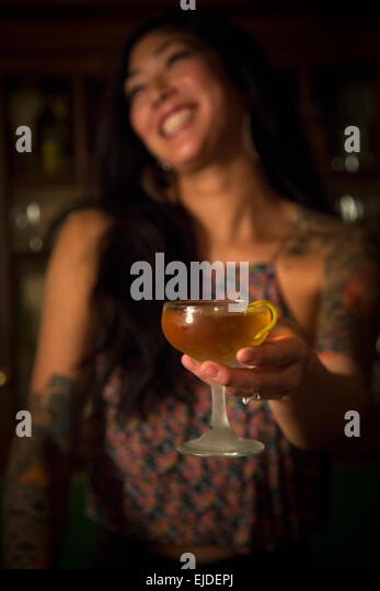 A woman holding a cocktail glass in a bar. - Stock Image