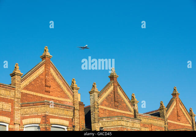 A plane coming in to land set against the Lion statues on the gables and gateposts of the 'Lion Houses' - Stock Image