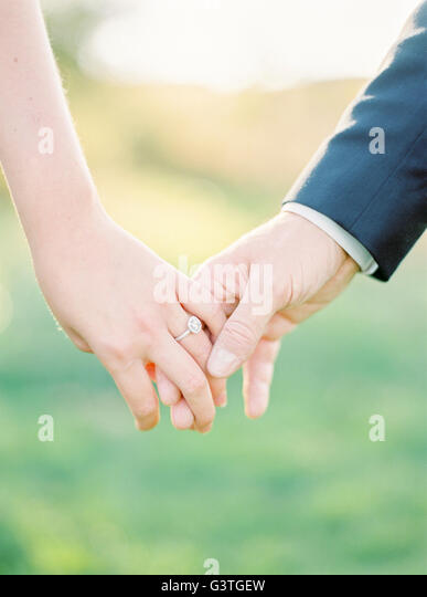 Sweden, Close-up of holding hands of newlyweds - Stock Image