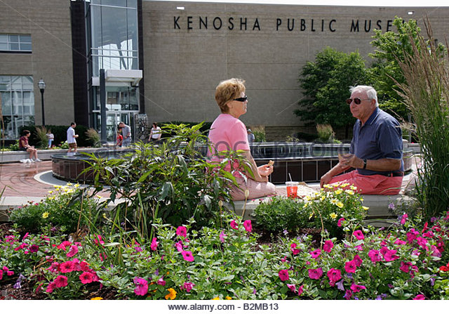 Wisconsin Kenosha Kenosha Public Museum man woman couple picnic flowers garden plaza summer - Stock Image