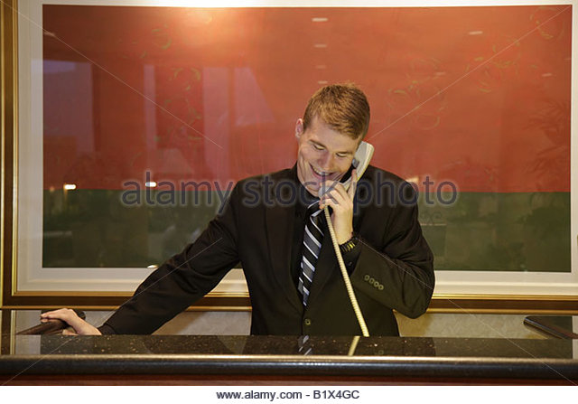 Little Rock Arkansas The Peabody Little Rock hotel lobby concierge supervisor man suit phone front desk job guest - Stock Image