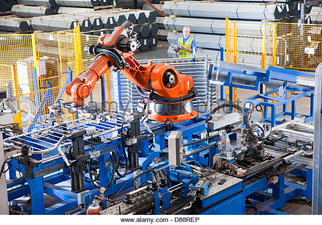 Worker controlling robotic machinery lifting steel fencing on production line in manufacturing plant - Stock Image