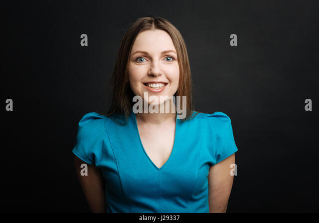 Cheerful young woman smiling in the black colored studio - Stock Image