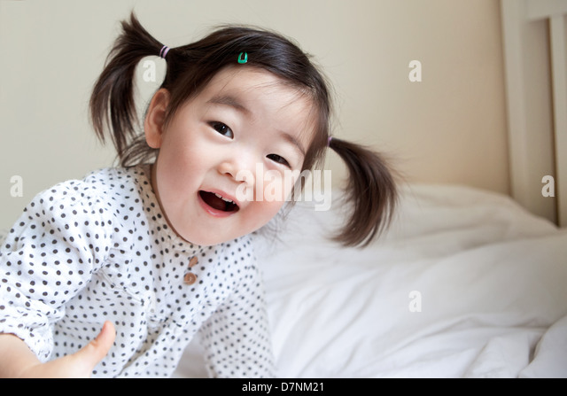Korean American toddler in pigtails smiling to camera in bedroom - Stock-Bilder