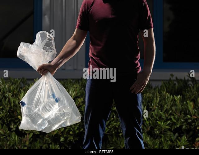 man carrying bag of water bottles - Stock Image