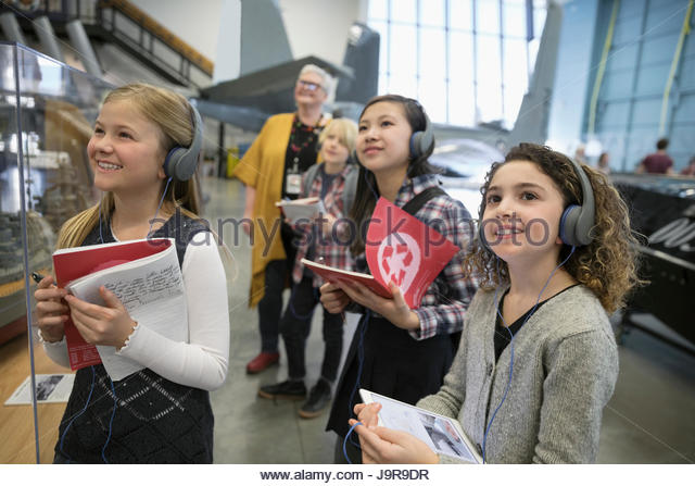Smiling, curious students wearing headphones and taking notes at exhibit on field trip in war museum - Stock-Bilder