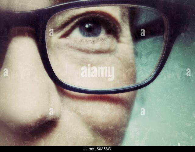 Eye of middle aged woman in spectacles, smiling, close-up - Stock Image