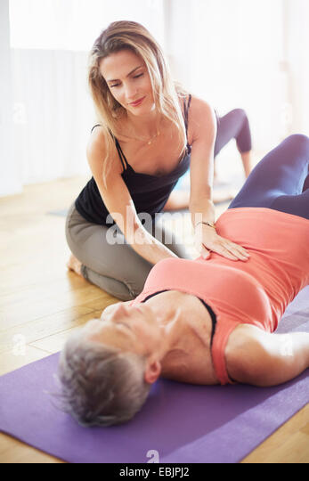 Teaching supporting mature student lying on back in pilates class - Stock Image