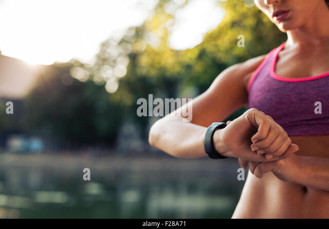Woman setting up the fitness smart watch for running. Sportswoman checking watch device. - Stock Image