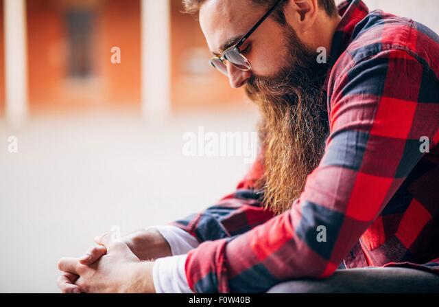 Side view of man with beard wearing sunglasses looking down - Stock-Bilder