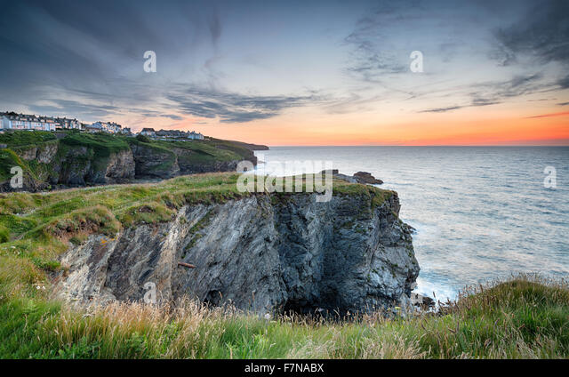 Beautiful sunset looking out at clifftop houses at Port Isaac on the rugged north Cornwall coast - Stock Image