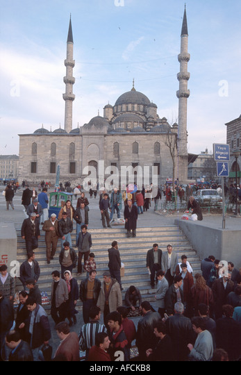 Turkey Istanbul Eminonu Square homeward bound workers Ottoman style Yeni Mosque built 1663 beyond - Stock Image