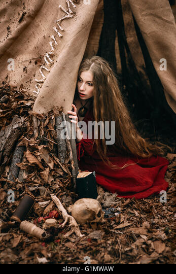 Young witch in the autumn forest - Stock Image
