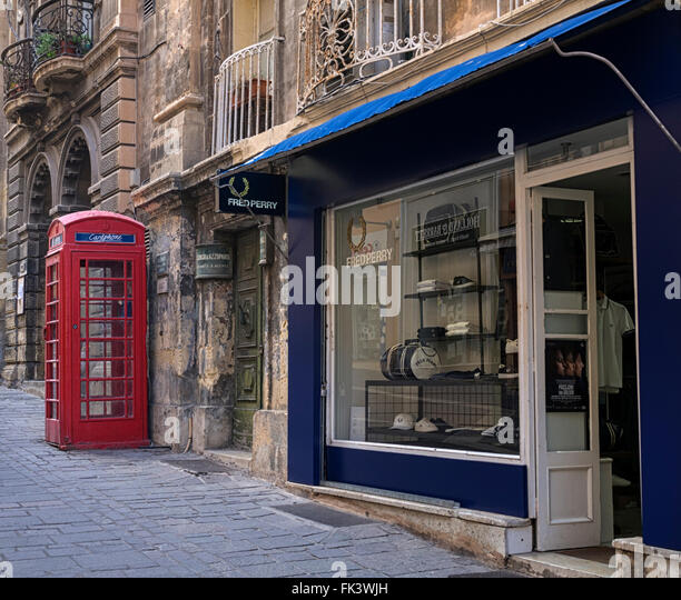 Signs of Britain: a red telephone box and Fred Perry clothing shop in Merchant Street, Valletta, Malta - Stock Image