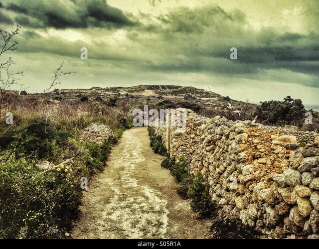 Storm clouds over country lane with dry stone walls - Stock Image