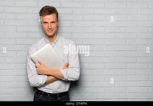 Portrait of cheerful Male holding computer, studio grey background looking camera - Stock Image