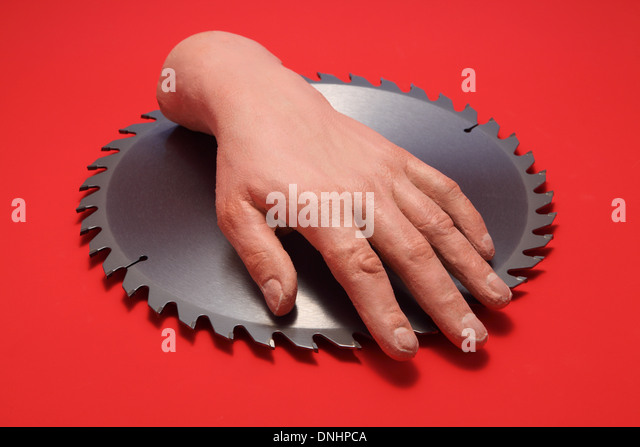 A fake human hand on a metal circular saw blade with a red background. - Stock Image