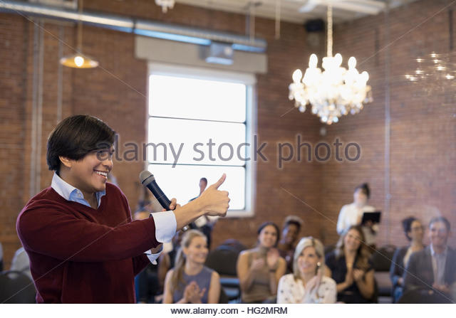 Enthusiastic businessman with microphone leading conference meeting gesturing thumbs-up - Stock Image