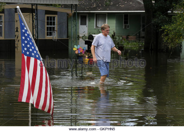 David Landaiche walks through flood water past an American flag in Sorrento, Louisiana, U.S., August 21, 2016.  - Stock-Bilder