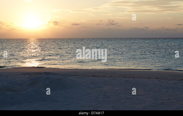 Sun Setting Over Beautiful Deserted Beach - Stock Image