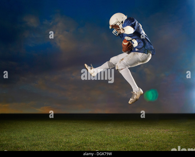 American football player jumping mid air - Stock-Bilder