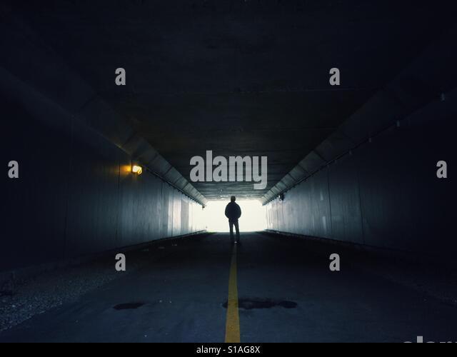 Man standing in the end of a dark tunnel - Stock-Bilder