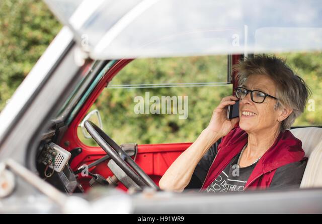 Elderly car mechanic making a phone call - Stock-Bilder