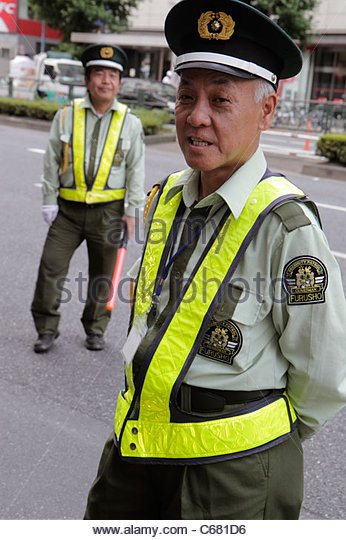 Japan Tokyo Shinjuku traffic guard security uniform Asian man men - Stock Image